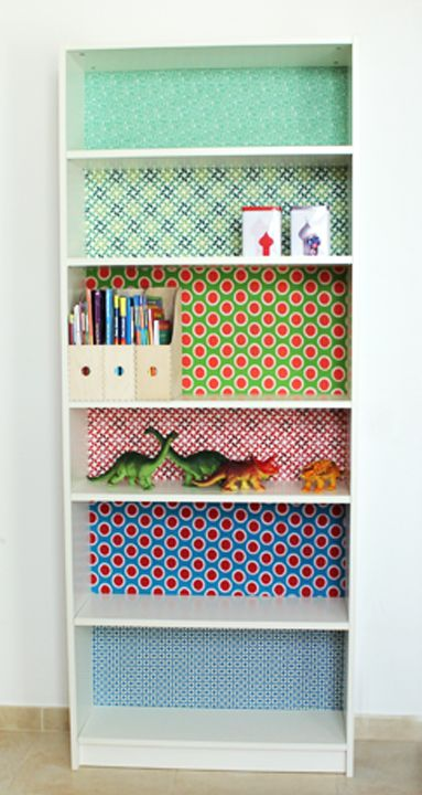 Wallpaper, wrapping paper, or contact paper inside the bookshelves.