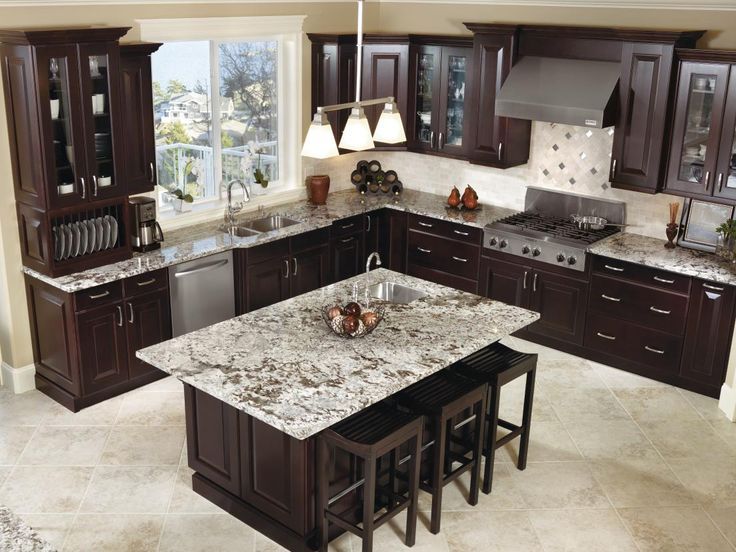 Gearing up to celebrate the new year? This kitchen has you covered! The large island with extra seating, stylish storage for dishware and hidden organization features make this kitchen an entertainer's dream. #KitchenCraftKitchens   Featured: Kitchen Craft's Brookfield cabinets with an Espresso finish.