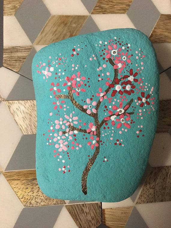 Hand painted river rocks collected in Southern Oregon. Sky blue back ground and cherry blossom tree.