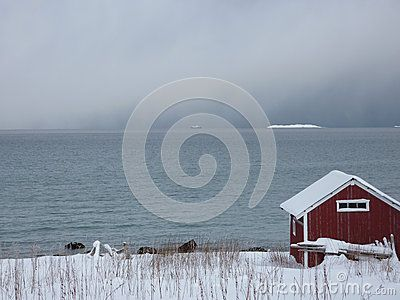 A boathouse by the sea in snowy weather in northern Norway.