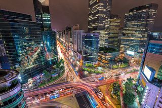 Traffic speeds through an intersection in the Gangnam district of Seoul on a rainy night.