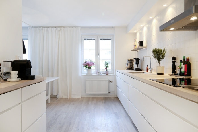 Long kitchen counter with bar stools. Long white curtains.