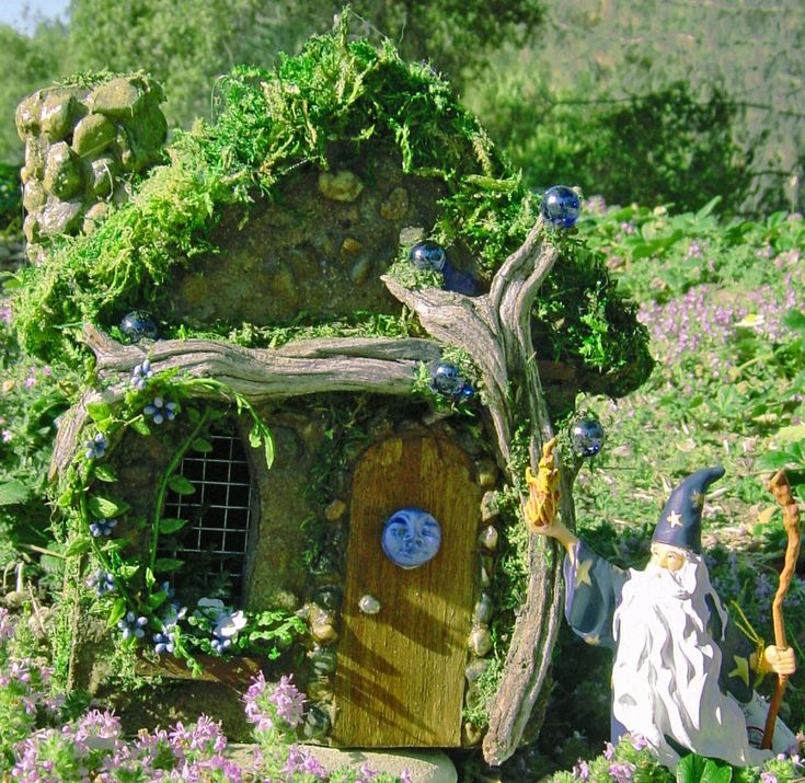 A celestial inspired blue moon fairy house with sparkling blue orbs and a tiny blue moon face.  This magical fairy house is pictured in our fairy garden with a little wizard.