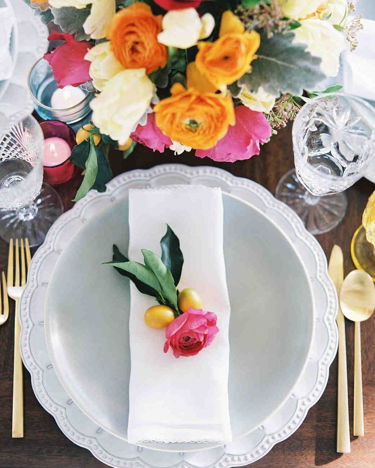 A Fiesta-Inspired California Welcome Dinner | Martha Stewart Weddings - Playing up the fiesta theme and keeping things laid-back, the tables were set with colorful centerpieces of ranunculus, roses, and tulips, amber-hued glass goblets, and modern gold flatware. They mixed up the place settings, with some being a bit more formal, like this pairing of white plates topped with a napkin and pairing of ranunculus and kumquats.