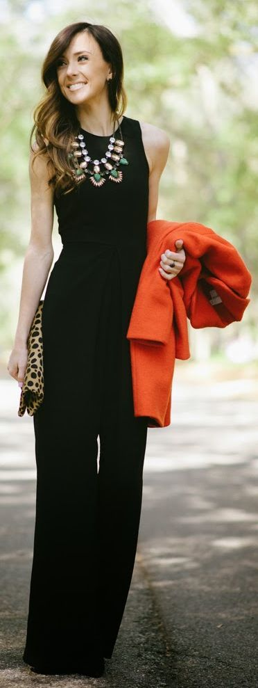 Street style | Black jumpsuit, orange coat, clutch, statement necklace: