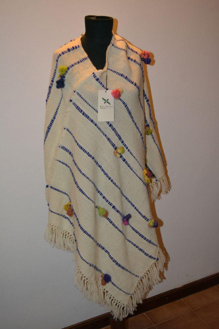 Poncho tejido en lana de oveja hilado fino con detalles en flamé de lana y pompones de vellón de lana