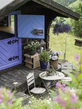 PAUSEPLASS: Blå harmoni mellom dør, blomster og krukker.