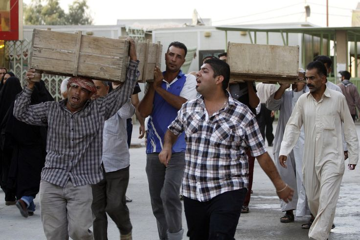 MOURNING: Men carried the caskets of bombing victims in Najaf, Iraq, Sunday. A wave of car bombings and other attacks in Iraq killed at leas...