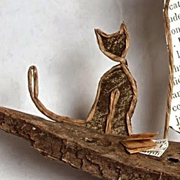 Chat en découpes de papier collées sous du kraft armé.