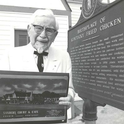1930  First Location: Corbin, KY  Bite of History: Harland Sanders's first outpost of Kentucky Fried Chicken, Sanders Court and Café, was located in the front room of a local gas station in Corbin, Kentucky. Word spread quickly that Sanders's special recipe for fried chicken cooked in an iron skillet was finger-lickin' good.