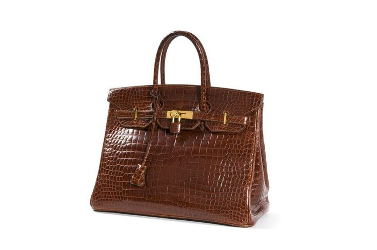 HERMES Paris made in france  Sac «Birkin» 35 cm en crocodile porosus Cognac, garniture en métal plaqué or, tirette, clochette, clefs cadenas gainé, intérieur doublé en chèvre marron comprenant une poche zippée et une poche plaquée, double poignée. Année: 1994.  Bon état général (légères petites usures aux angles). Dans sa boîte.  A Cognac porosus «Birkin» bag, 35 cm, gilt metal hardware, keyfob & padlock, double handle.  Year: 1994.  Good overall condition (slightly used corners). In its…