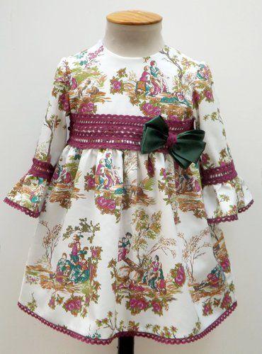 Vestido para bebe niña de toilé en tonos buganvilla ymanga francesa, adornado con encaje de bolillos y un lazo verde a juego. Talle alto