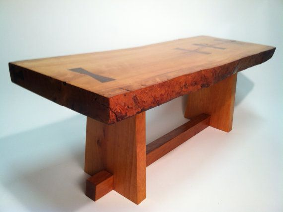 "This live edge coffee table was inspired by George Nakashima. It is solid cherry with walnut butterflies. Its long edges are highly textured. Sap wood is rarely this red. The wood will darken with age and achieve a beautiful patina. This museum quality table measures 42"" L x 15 1/2"" H x 16"" H (approximate)"