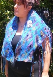 This stunning scarf can also be worn as a skirt, created by Artistic Ballistic. This particular piece has layers of felt criss crossed over the body of the fabric with tassels off the edges. $50