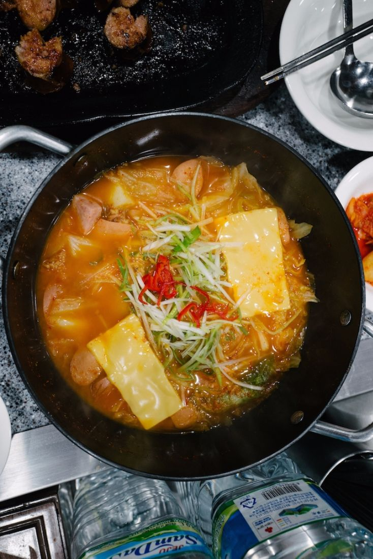 """38 best restaurants in Seoul - find Budae-jjigae (""""army base stew"""") is a popular stew in Korea made with sausage, ham, baked beans, and kimchi. It is believed to originate from the post-Korean War period, when it was made with surplus food from U.S. Army bases. Want to try the famous sausage stew but cannot stand the heat? Bada Sikdang offers a milder version called Johnson Tang (yes, named after President Lyndon Johnson), toned down with loads of cabbage and sliced cheese."""