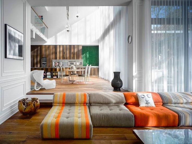 Cuisine en bois moderne et ouverte sur le salon avec canapé modulable en gris et orange
