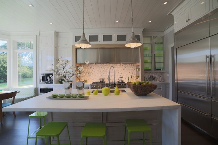 Contemporary kitchen features white vintage light pendants illuminating white marble top island framing sink paired with restaurant style pull-out faucet lined with lime green barstools situated across from industrial stainless steel refrigerator and freezer. White plank ceiling stands over a row of glass front cabinets stacked over stainless steel hood above mosaic tiled backsplash and stainless steel stove flanked by built-in spice nooks. To the left of cooktop is a built-in coffee…