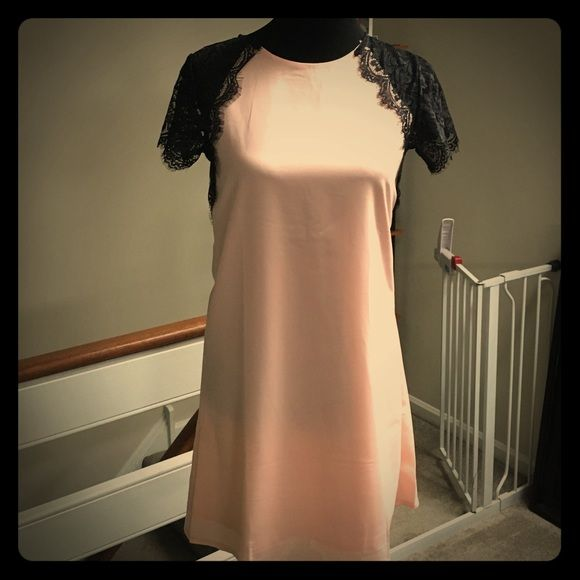 "Pale pink dress with black lace sleeves Size large pale pink dress with black lace sleeves. Runs small in my opinion and is 31.5"" long. Dresses"