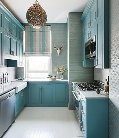 Love the turquoise shade of these recessed-panel kitchen cabinets!