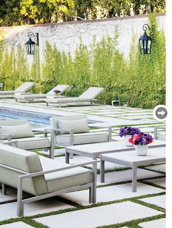 Low-profile indoor-outdoor furniture by the pool has a contemporary Californian vibe. Coach-style lamps add character and provide ambient light. {PHOTO: Donna Griffith}