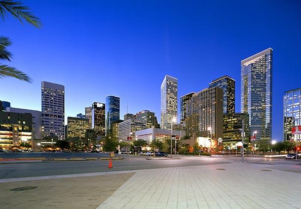 Encuentra tu hotel en Houston y disfruta del horizonte iluminado del centro de Houston al anochecer.