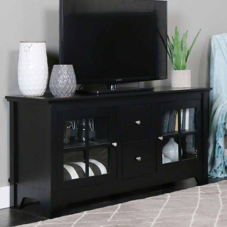 Update your living room decor with this modern solid wood TV stand. The stand, which accommodates most 52-inch TVs, features two drawers for video game and DVD storage and two glass doors with adjustable shelves to hold your electronic components.