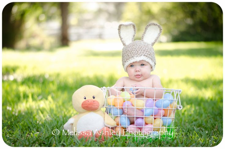 Hoppy Easter photo shoot. Baby in bunny hat, sitting in basket of plastic eggs. Stuffed duck. Lawn. Melissa Ashley Photography.