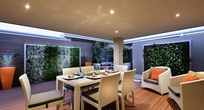 Vertical gardens and energetic orange bring this alfresco area to life.