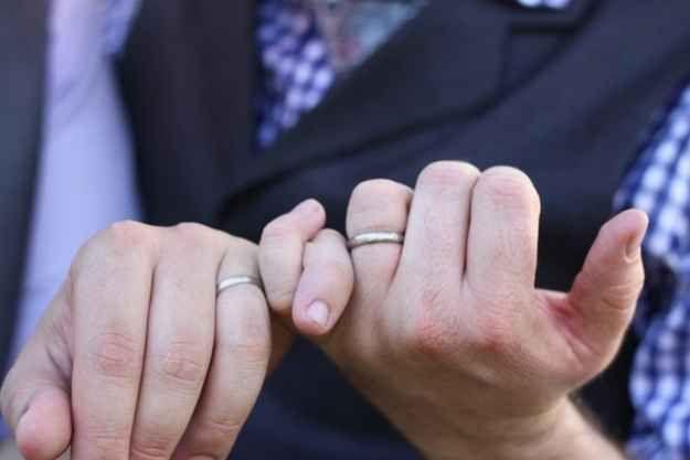 Una foto de una promesa de meñiques mostrando sus anillos. | 42 ideas para fotos de boda increíblemente divertidas que vas a querer copiar