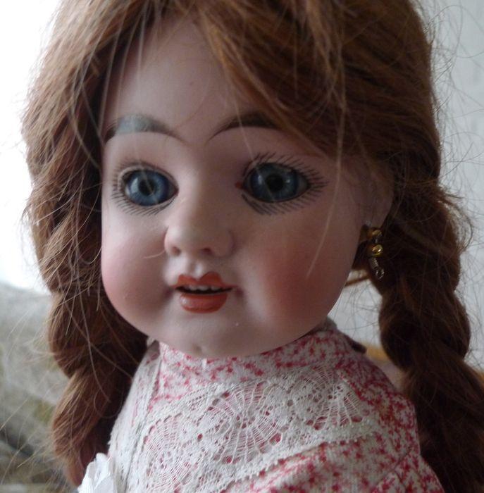 Hoogstwaarschijnlijk is dit een pop uit de fabriek van Max Räder, Sonneberg. Een vrij kleine porseleinfabriek die bekend stond om zijn mooi afgewerkte poppenkoppen. Ze is heel mooi beschilderd met prachtige wenkbrauwen en wimpers Ze heeft geen haarlijnen en is helemaal gaaf De pop is helemaal gekleed in ondergoed, kousen en schoentjes. Ze heeft een mooie jurk aan met veel kant en strikken. Ze heeft prachtige blauwe paperweight ogen en gaatjes in haar oren.  Ze heeft nog alle vingertjes en…