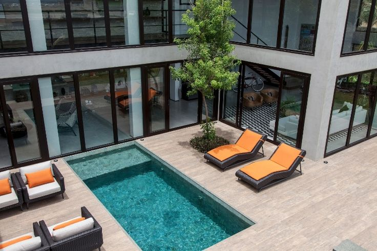 Na área externa, o piso é de porcelanato Ecowood Canela Portobello. A piscina de pedra lisa Hijau é rodeada por móveis de fibra da Casual Home Design. A casa em Salvador (BA) tem projeto de Sidney Quintela do SQ  Arquitetos Associados