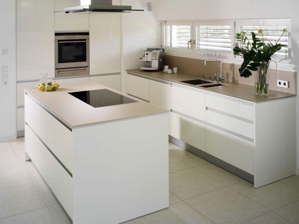Glazen werkbladen in een moderne keuken. Je zou het misschien niet meteen denken, maar de dunne werkbladen in deze keuken zijn gemaakt van glas! Door de dichte structuur is glas een heel hygiënisch materiaal om werkbladen van te maken. Er kunnen immers geen bacteriën of geurtjes intrekken.