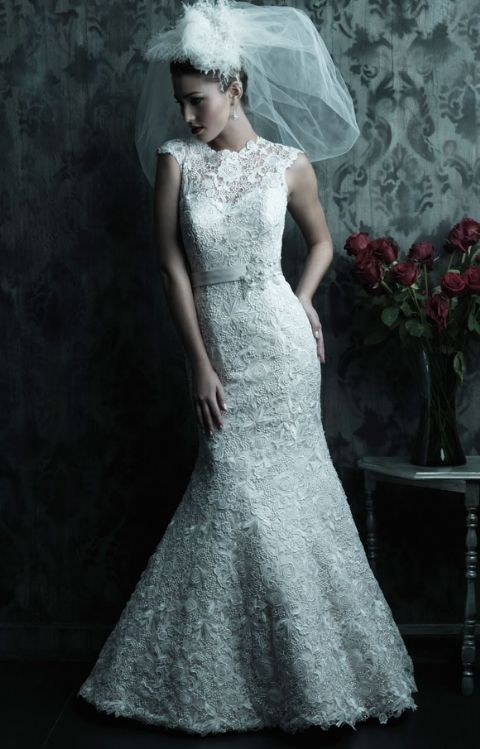 Allure Bridal- C226: This fitted slim gown in all-over Venice lace features a beautiful raised neckline with a dramatic V-shaped back. A chapel length train and covered buttons complete this elegant style.