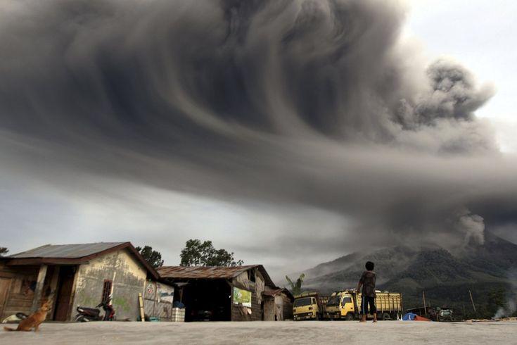 ASH SWIRLS: A villager watched as Mount Sinabung spewed ash near Karo district, Indonesia on November 18, 2013 | © Roni Bintang | Reuters