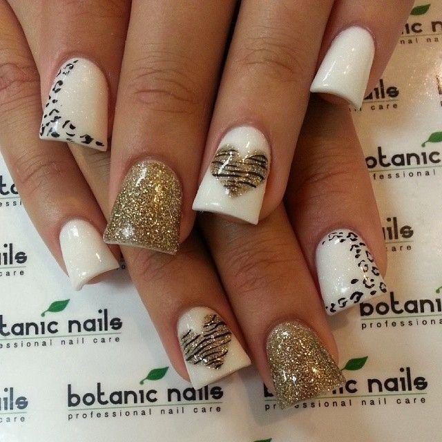 Lindas uñas con brillos blancos y dorados, decoradas con estampados de leopardo, algunas adornadas con corazones con estampado de zebra.