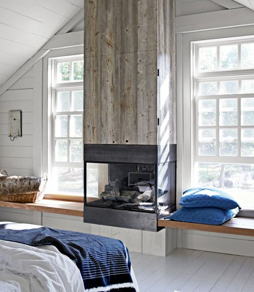 Faced with reclaimed white pine, the gas fireplace's chimney hides a surprise: a flat-screen TV.