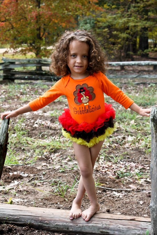 """She will look absolutely scrumptious in this Thanksgiving themed TuTu One Piece by Moxie Couture!    Our orange one piece is accented with alternating red, brown and yellow soft chiffon; a wonderful combination of autumn colors! Our embroidered turkey applique is sewn onto the orange one piece, this design will not scratch or irritate your baby girls sensitive skin.    Underneath our yummy turkey design, we have spelled out """"Gobblelicious"""" in jet black rhinestones."""