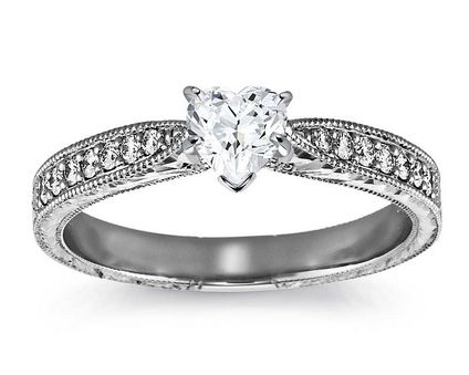 Inspired by vintage design, this diamond engagement ring in 14k white gold features millgrained edges that frame an engraved motif set with fourteen petite round diamonds to frame your centre diamond. The centre diamond is a colourless natural stone that has an elegance and sparkle second to none. This is truly a classic vintage design that will make you stand out from the crowd. Total diamond weight 0.65ct. (0.51ct Centre, 0.14ct Shoulders) D VS1 www.wgjewellery.com