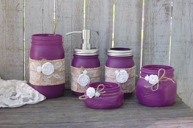 Rustic mason jar bathroom jar set. Hand painted in plum, wrapped with burlap and lace, tied with jute and white roses, finished with a protective coating. Metal soap dispenser, toothbrush holder, make