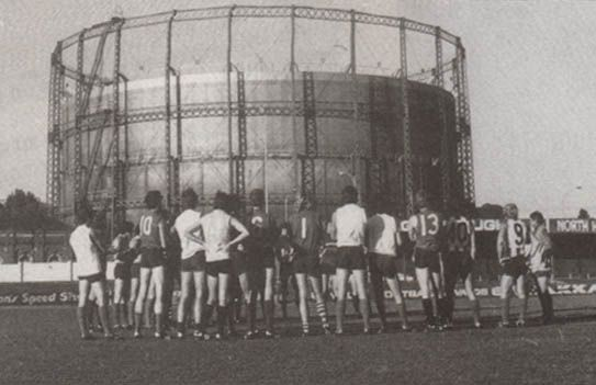 The gasometer at North Melbourne Football Club's ground at Arden St. I can recognise Barry Cable, Lurch Goodingham, jughead Cowton!