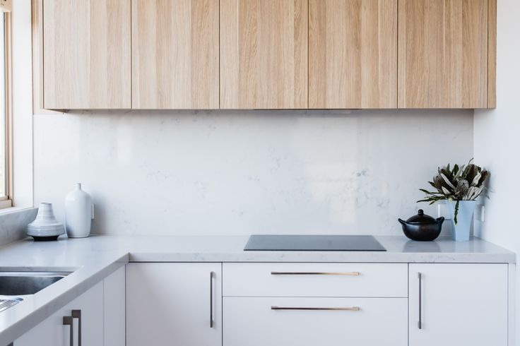 Carrara Smartstone with Natural Oak Ravine overhead cabinets. Kitchen by Zeev. Designed and styled by The Den Interiors