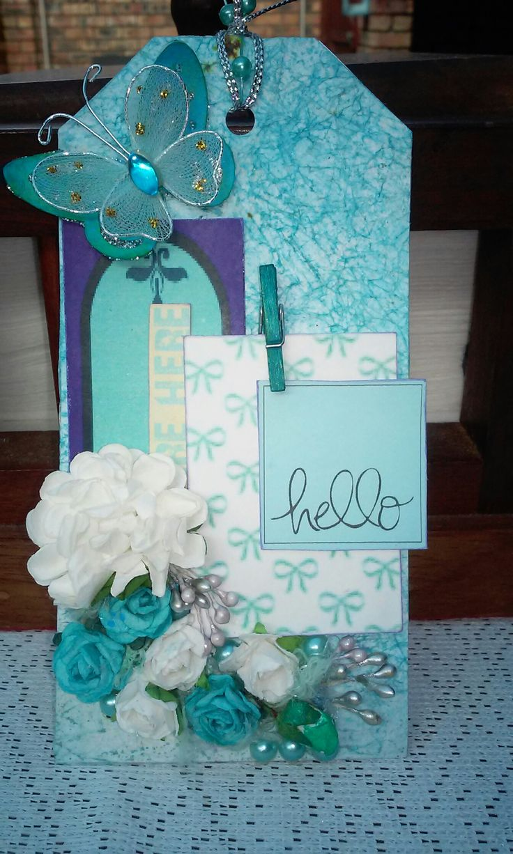 Tag idea in blue and white. Layered paper accents with flowers. Wax paper background.