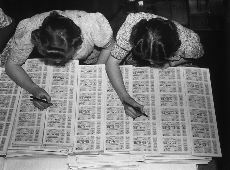 circa 1939:  Two women checking FA cup final tickets at Messrs Waterlow's printing works in Finsbury, London.  (Photo by Hulton Archive/Getty Images)