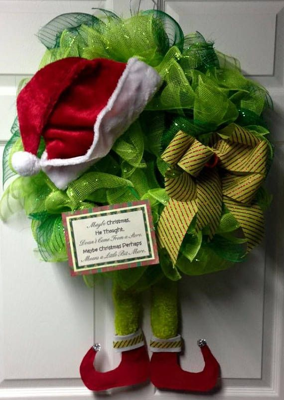 The Grinch is here! One of our most popular items at our local craft fairs. This mesh wreath measures 22 and is extremely full. He is adorned with dangly legs with fluffy trim, Santas hat, hand tied bows and a quote from the Grinch film.