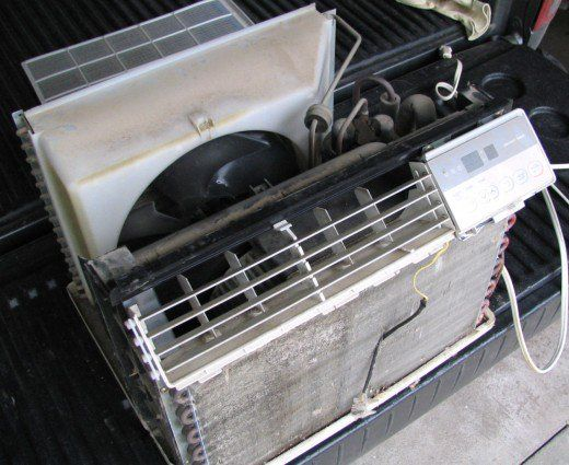 Removing the case exposes the coils, fan, and compressor. In a larger window unit, after the front plastic and a few screws are removed, the air conditioner will slide out of the case toward the inside of the room.