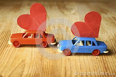 Miniature plastic cars carrying a red heart