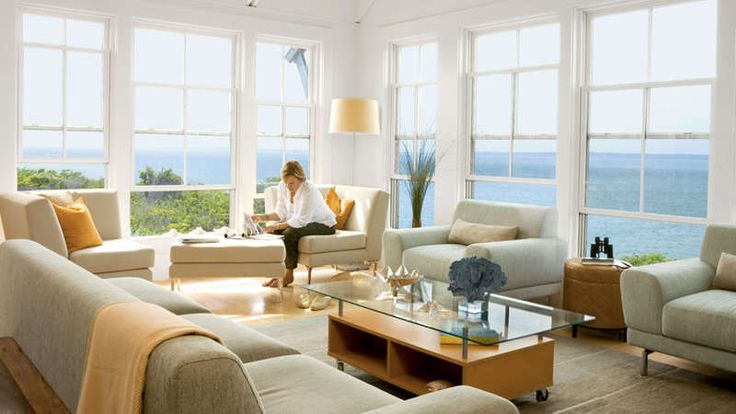 Pale sea green linen couches and chairs blend into this light and bright room with its wall of windows