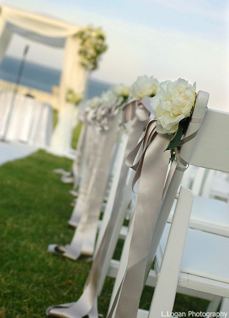 taupe satin ribbons hanging from white garden chairs ...
