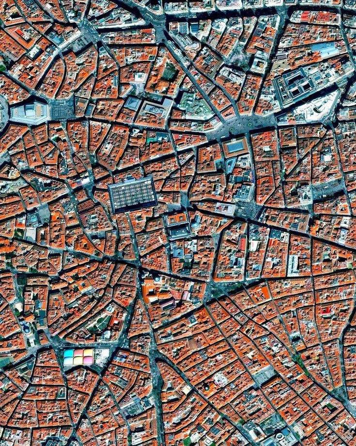"""La Latina is a neighborhood located in the center of Madrid, Spain. The area was named after an old hospital of the same name that was founded in 1499. In the lower left of this Overview, you can also see the popular Mercado de la Cebada market, with its six-panel, multi-colored rooftop.  Instagram: https://bit.ly/2Hnl7I5  40°24'41.4""""N, 3°42'39.5""""W  Source imagery: DigitalGlobe"""
