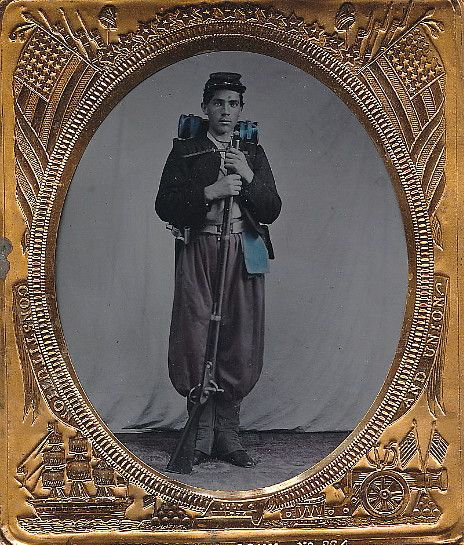 *ZOUAVE SOLDIER:in typical style garb. Sporting red pantaloons tucked into his gaiters,blue sash is worn around the waist over which is a white buff waist belt.The face of the plate is obscured by the positioning of his rifle but appears to be a scriptNewYork plate.The jacket is of a darker material which I assume was blue,cut in the typical Zouave style.He stands w/his musket in front of him+ his knapsack strapped tightly to..His bedroll+ rubber blanket peering out above his shoulders.